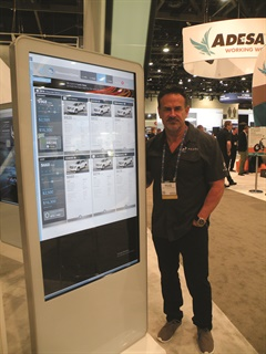 "Pearl Technologies' Bruce Thompson poses next to the company's new ""Genius Stations,"" a six-foot-by-four-inch touchscreen display that runs the company's ShowroomXpress retail platform. Aside from digitizing the sales and finance processes, the system incorporates a dynamic F&I menu."