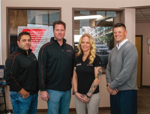Sales professional Tracy Heid is flanked by (from left) owners Steve Ganser and pat McNamar and General Sales Manager Bryan Popp in Mad City Mitsubishi's showroom.
